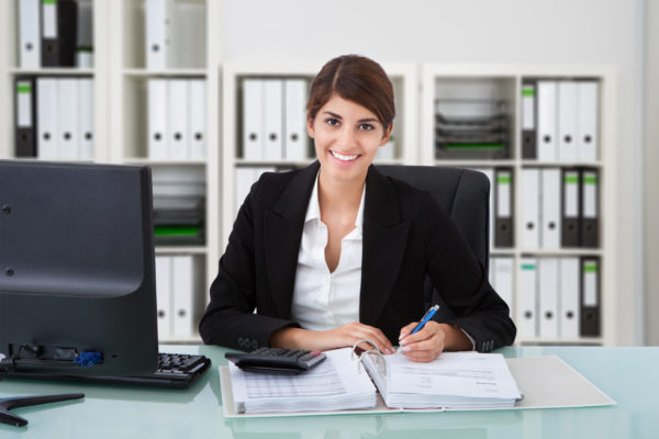 Smiling female accountant prepares a client's financial statements at her desk.